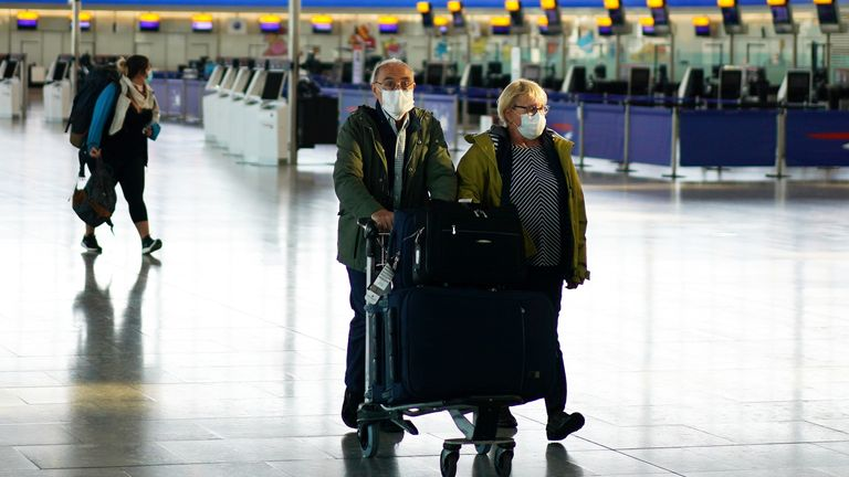 People wearing masks are seen at Heathrow airport