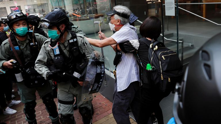 An anti-government demonstrator argues with riot police