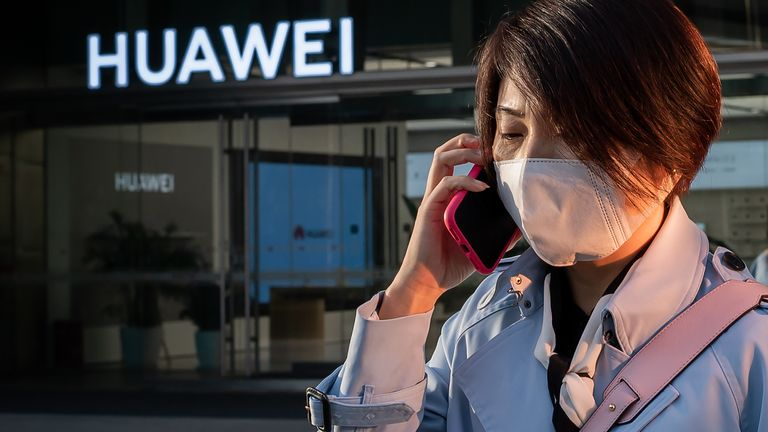 A woman wearing a wearing a facemask as a preventive measure against the COVID-19 coronavirus speaks on her smartphone outside a shopping mall past a Huawei shop (back) in Beijing on April 1, 2020.
