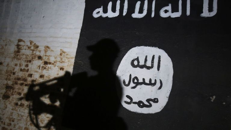 A member of the Iraqi forces walks past a mural bearing the logo of the Islamic State (IS) group