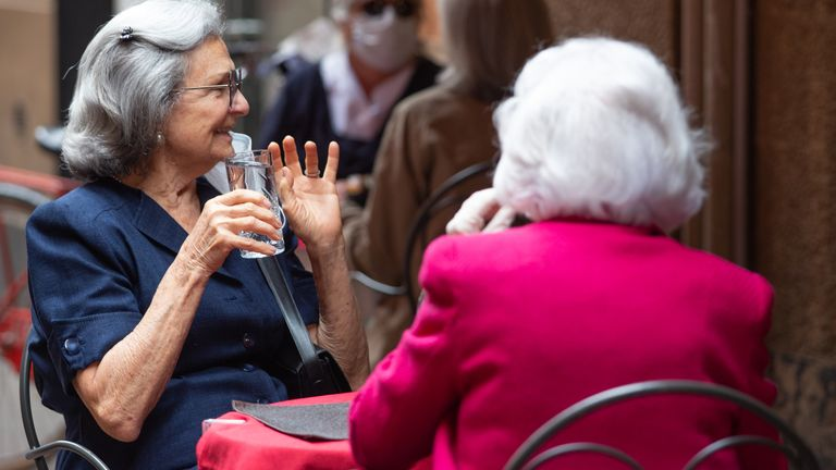 Women are seen enjoying a drink al fresco as Italy began easing lockdown on 18 March