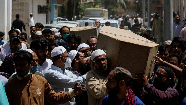 People carry the coffins of husband and wife who were killed in a plane crash, during a funeral in Karachi