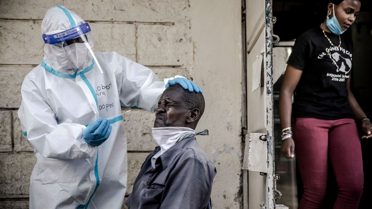 A health worker wears personal protective equipment (PPE) while collecting a nasal swab in Kenya