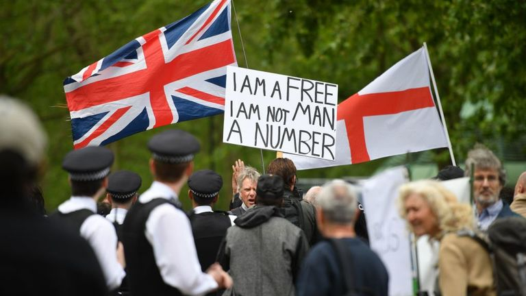 "Police attend an anti-coronavirus lockdown demonstration with protesters holding a Union Flag (L), a Flag of St George (R) and a placard that reads ""I am a free man, I am not a number"" in Hyde Park in London on May 16, 2020, following an easing of lockdown rules in England during the novel coronavirus COVID-19 pandemic. - Fliers advertising 'mass gatherings' organised by the UK Freedom Movement to oppose the government lockdown measures and guidelines put in place to halt the spread of coronavir"