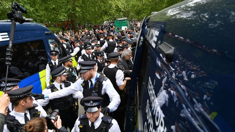 Piers Corbyn (C - grey top), brother of former Labour Party leader Jeremy Corbyn, is led away by police officers into a police van at an anti-coronavirus lockdown demonstration in Hyde Park in London on May 16, 2020, following an easing of lockdown rules in England during the novel coronavirus COVID-19 pandemic. - Fliers advertising 'mass gatherings' organised by the UK Freedom Movement to oppose the government lockdown measures and guidelines put in place to halt the spread of coronavirus in pa