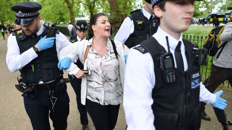 A woman is arrested by police officers at an anti-coronavirus lockdown demonstration in Hyde Park in London on May 16, 2020, following an easing of lockdown rules in England during the novel coronavirus COVID-19 pandemic. - Fliers advertising 'mass gatherings' organised by the UK Freedom Movement to oppose the government lockdown measures and guidelines put in place to halt the spread of coronavirus in parks around the UK calling for attendees to bring a picnic and music have been circulating on
