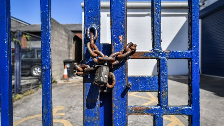 A rusty chain and padlock secure blue painted steel gates to prevent access to a business