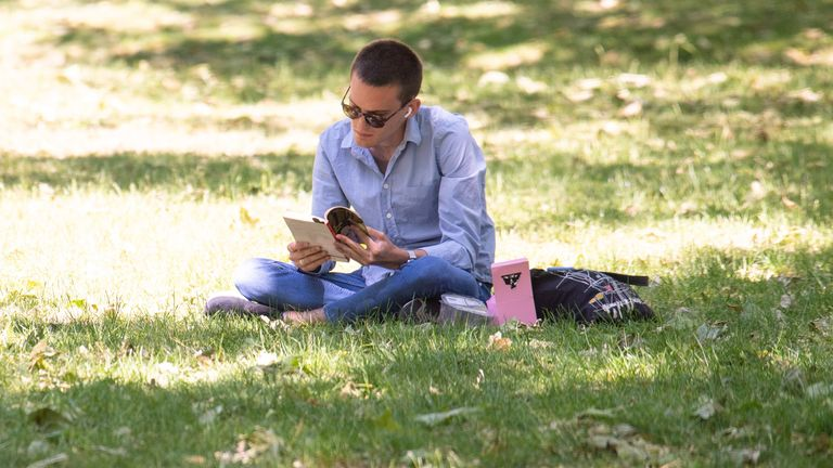 A man reads a book at St James Park in London