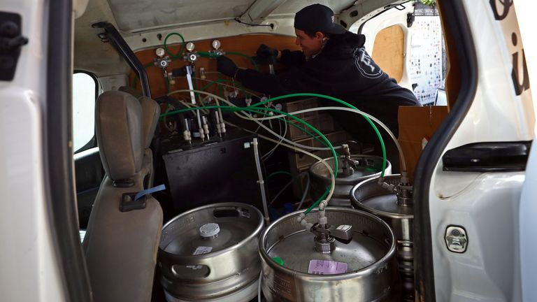 The beer kegs are loaded into the back of the van