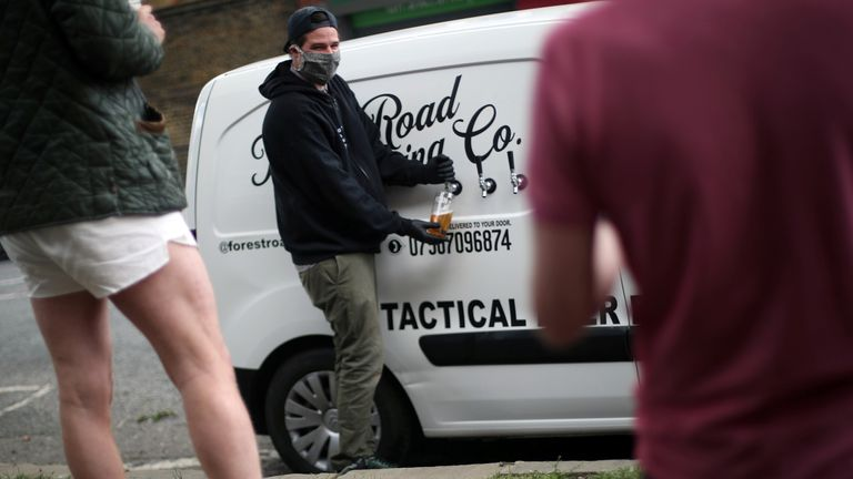 Peter Brown pours a customer a pint of beer during his delivery round in Hackney, east London