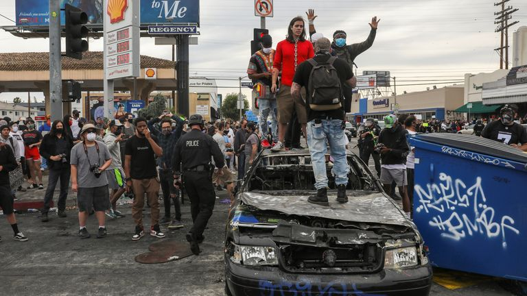 Demonstrators stand on top of a burned out police car in Los Angeles
