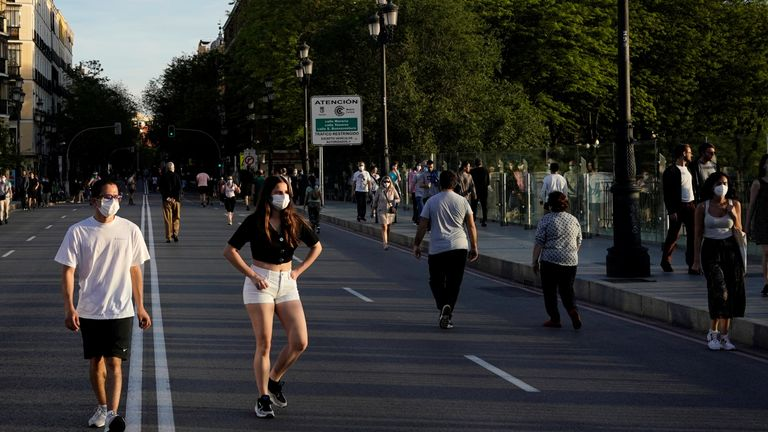 People wearing face masks walk along a street, as the spread of the coronavirus disease (COVID-19) continues, in Madrid, Spain, May 3, 2020