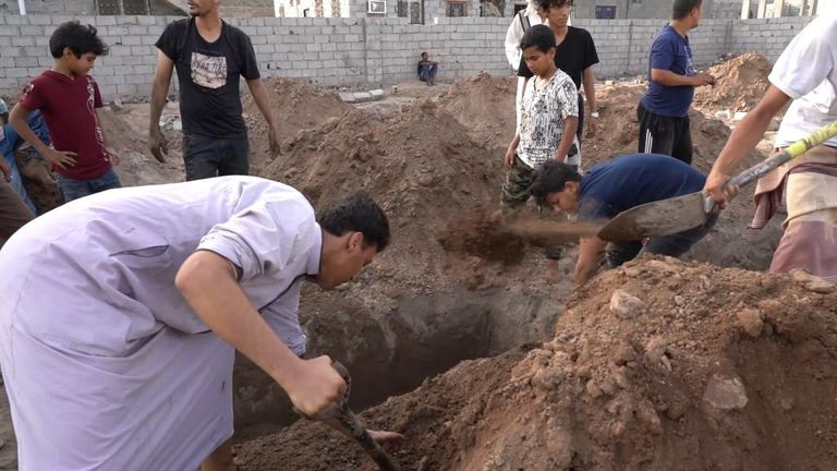 Men dig the graces by hand at Radhwan cemetery