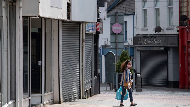 A woman wears a face mask and surgical gloves while carrying a bag and walking passed closed small businesses on High Street