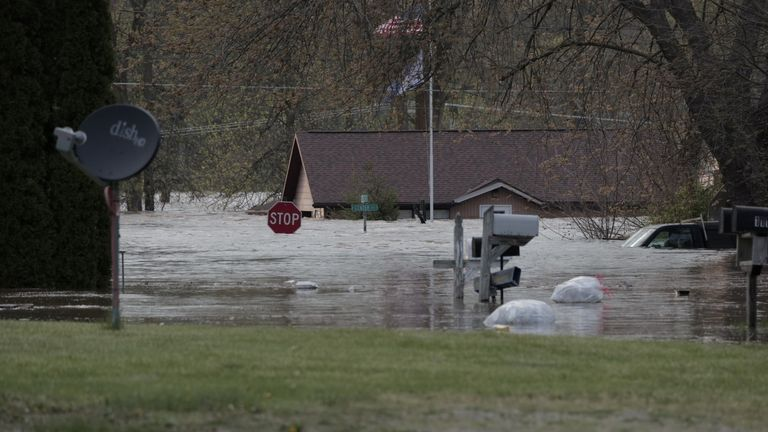 Vehicles and signs are submerged in downtown Sanford, Michigan, after a nearby dam burst