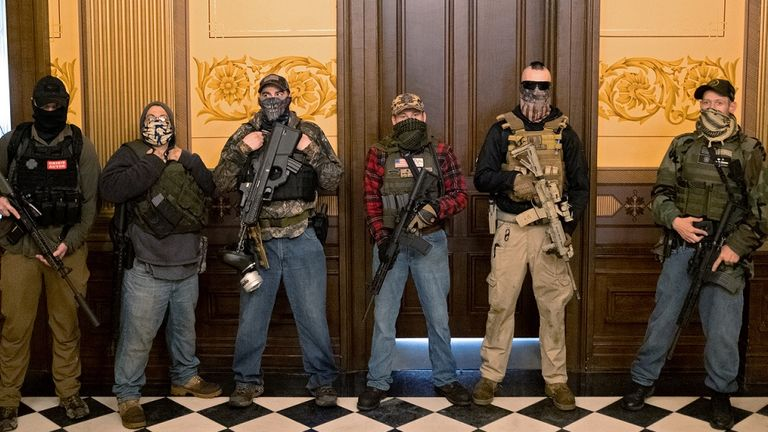 A militia group with no political affiliation from Michigan stands in front of the Governor's office