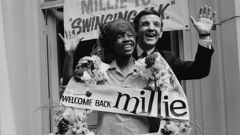 Australian-born British disc jockey Alan 'Fluff' Freeman (1927 - 2006) welcomes Jamaican singer Millie Small back to the 'swinging UK', 1964. (Photo by Evening Standard/Hulton Archive/Getty Images)