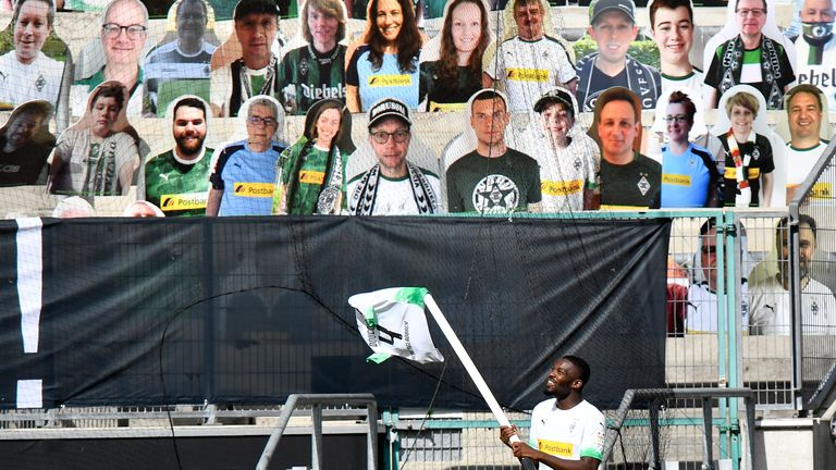 Moenchengladbach's Marcus Thuram celebrates in front of the cardboard cut outs with photos of Moenchengladbach fans displayed on the stands during the Bundesliga match between Borussia Moenchengladbach and 1. FC Union Berlin at Borussia-Park on May 31, 2020 in Moenchengladbach, Germany
