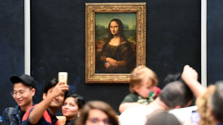Visitors take pictures in front of Mona Lisa after it was returned at its place at the Louvre Museum in Paris on October 7, 2019