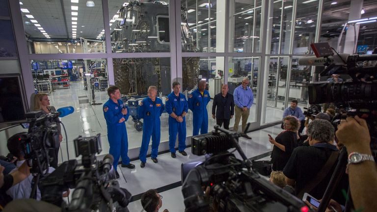 HAWTHORNE, CA - AUGUST 13: (L-R) NASA Astronauts Bob Behnken, Doug Hurley, Mike Hopkins and Victor Glover, and Director of Crew Mission Management Benji Reed talk to reporters in front of the Crew Dragon spacecraft, under construction in a clean room, during a media tour of SpaceX headquarters and rocket factory on August 13, 2018 in Hawthorne, California. SpaceX plans to use the spaceship Crew Dragon, a passenger version of the robotic Dragon cargo ship, to carry NASA astronauts to the Internat