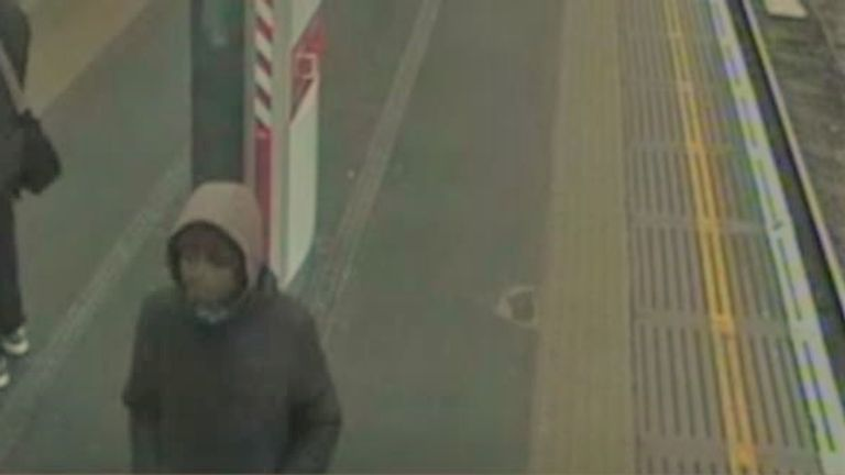 The man is described as black, aged around 20, wearing grey tracksuit bottoms, a grey hoodie with a dark jacket and dark cap