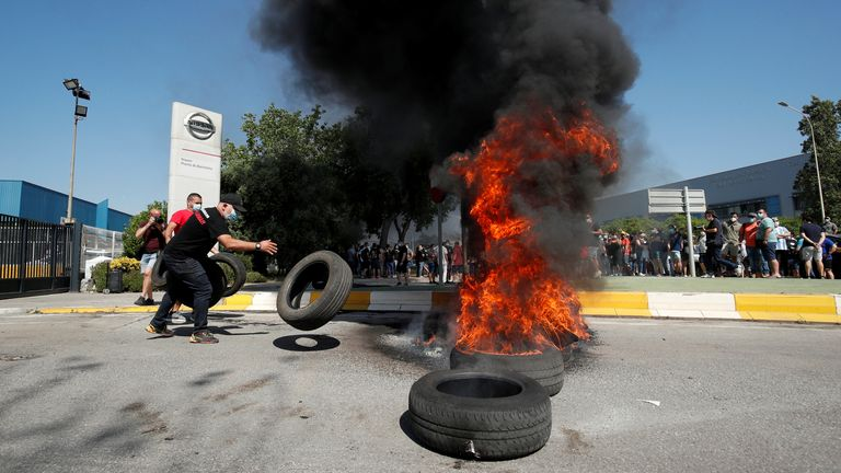 Nissan worker throws a tire on a burning pile during a protest in front of the Barcelona factory