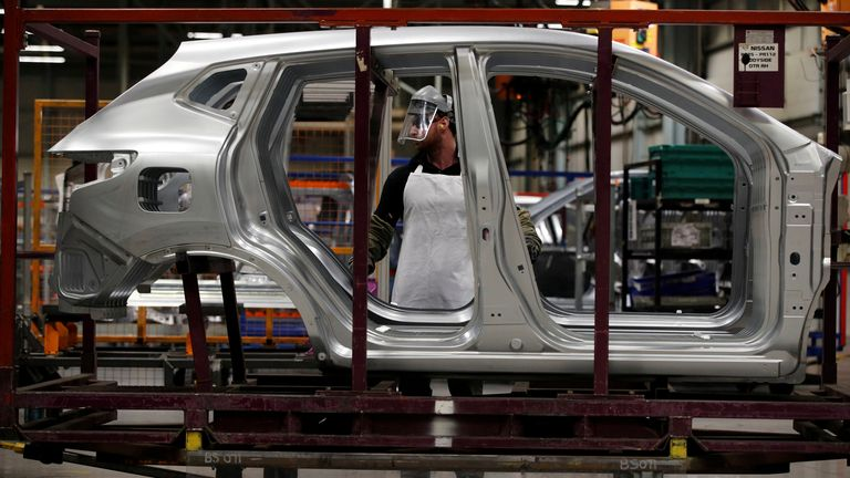 Workers are seen on the production line at Nissan's car plant in Sunderland