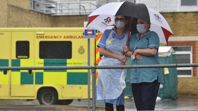 Two nurses stand under an umbrella during the pouring rain outside Southend Hospital during the minute's silence for key workers who have died during the Coronavirus on April 28, 2020 in Southend on Sea