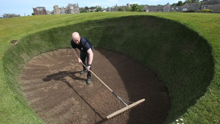 Sandy Reid rakes the Road Hole bunker on the Old Course at St Andrews