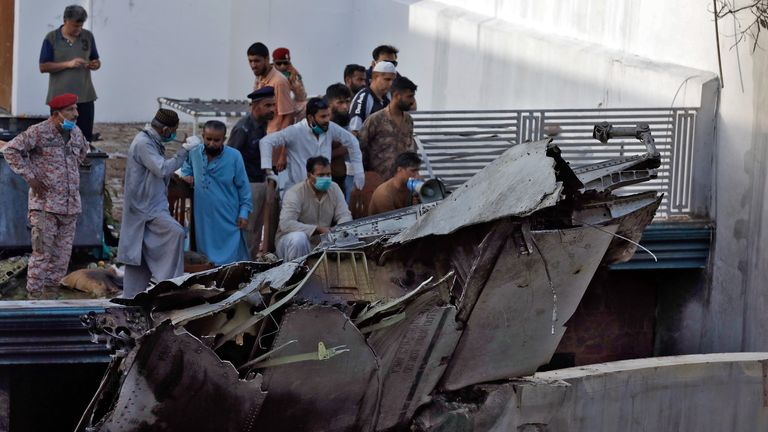 People stand next to the debris of a plane after crashed in a residential area near an airport in Karachi, Pakistan May 22, 2020. REUTERS/Akhtar Soomro