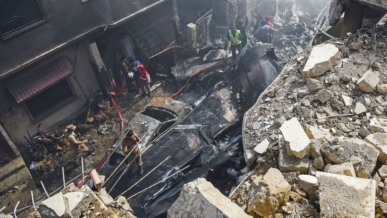 Rescue workers gather at the site after a Pakistan International Airlines aircraft crashed in a residential area in Karachi on May 22, 2020. - A Pakistani plane with nearly 100 people on board crashed into a residential area in the southern city of Karachi on May 22, killing several people on the ground. (Photo by Rizwan TABASSUM / AFP) (Photo by RIZWAN TABASSUM/AFP via Getty Images)