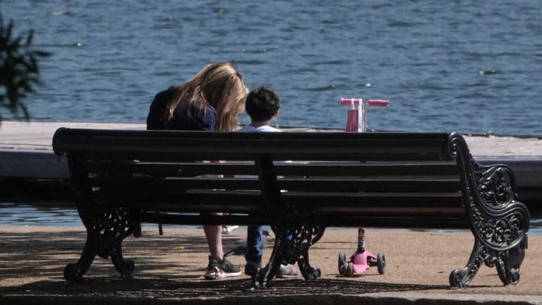 A woman and a young child sit on a bench in London