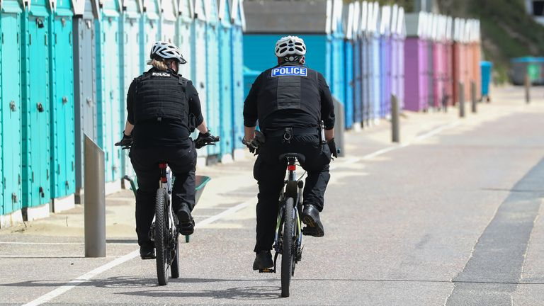 Police officers on bicycles patrol Bournemouth beach in Dorset