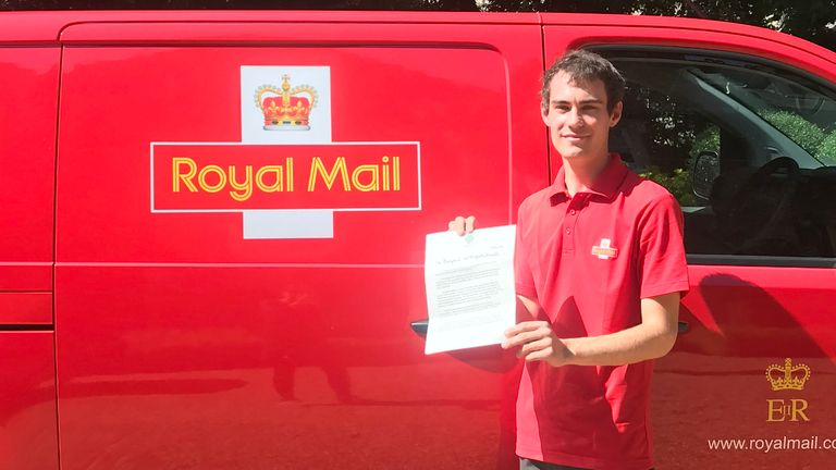 Postman Daniel Edwards holds the letter from the Prince of Wales and the Duchess of Cornwall