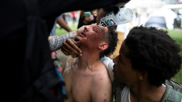 A man has water poured into his eyes as protesters march in Denver