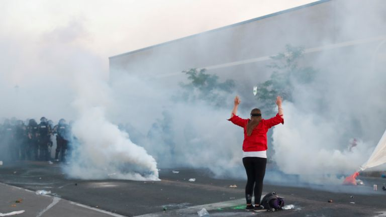 A demonstrator raises her arms in front of security forces in Minneapolis