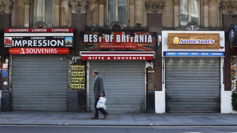A man is seen passing a closed souvenir shop