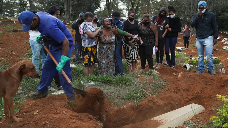 Relatives react during the burial of 64-year-old Raimunda Conceicao Souza, who died from COVID-19, at Vila Formosa cemetery, Sao Paulo