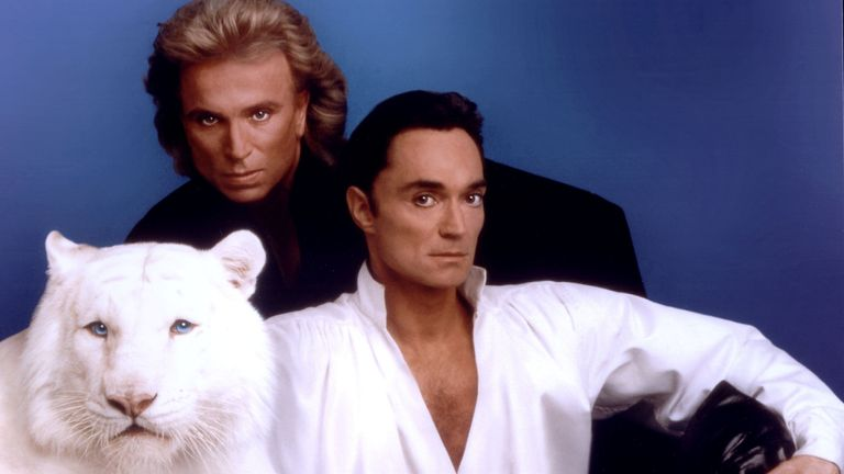 Siegfried (L) & Roy pose with a white tiger in this undated photo