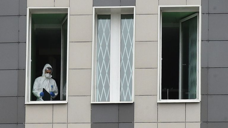 A medic wearing protective gear looks out from a window of the Saint George hospital after a fire broke out in the medical facility in Saint Petersburg