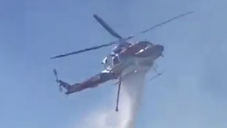 Chopper drops retardant on raging wildfire in California