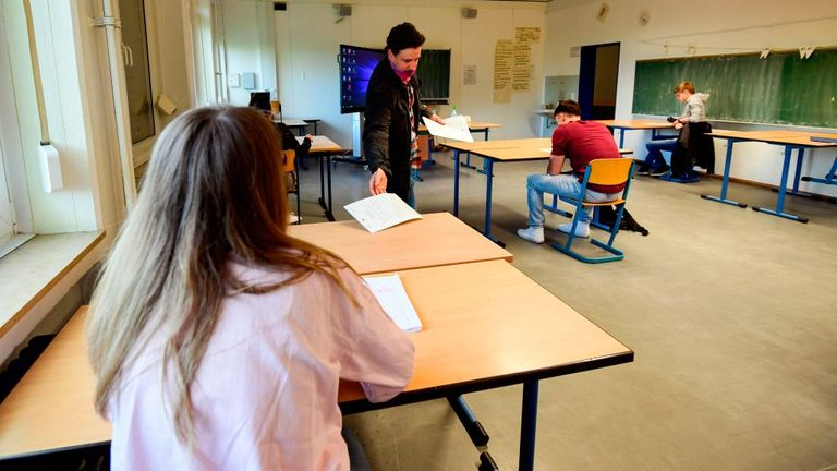 A teacher talks to few pupils who are socially distancing preparing in their school in Dortmund