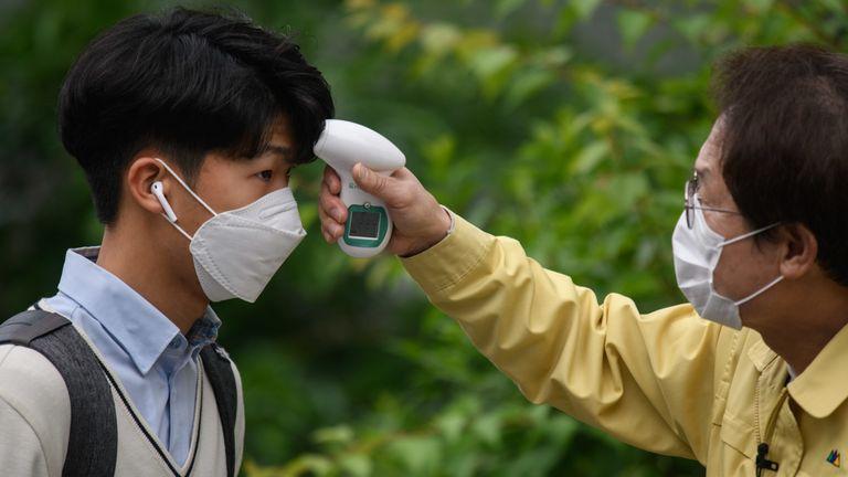 Alunos usando máscaras são submetidos a verificações de temperatura em Seul, Coréia do Sul