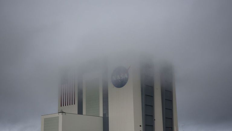 The massive Vehicle Assembly Building is shrouded in fog as stormy weather greeted launch day at the Kennedy Space Center in Florida on May 27, 2020. - A new era in space begins Wednesday with the launch by SpaceX of two NASA astronauts into space, a capability that for six decades symbolized the power of a handful of states, and which the United States itself had been deprived of for nine years.If the bad weather clears, at 4:33 pm (20:33 GMT) a SpaceX rocket with the new Crew Dragon capsule on