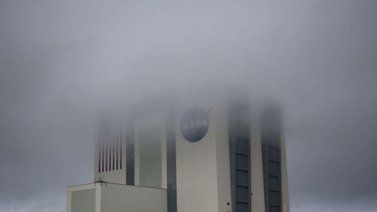 El enorme edificio de ensamblaje de vehículos está cubierto de niebla cuando el clima tempestuoso recibió el día del lanzamiento en el Centro Espacial Kennedy en Florida el 27 de mayo de 2020. - Una nueva era en el espacio comienza el miércoles con el lanzamiento por SpaceX de dos astronautas de la NASA al espacio, una capacidad que durante seis décadas simbolizaba el poder de un puñado de estados, y de los cuales los Estados Unidos habían estado privados durante nueve años. Si el mal tiempo se despeja, a las 4:33 pm (20:33 GMT) un cohete SpaceX con el nuevo Crew Dragon cápsula en