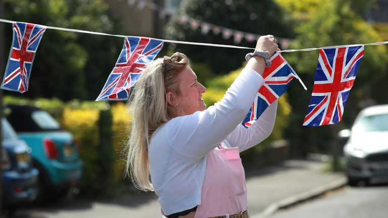 Local resident Clarrie Jackson prepares the flag bunting on May 07, 2020 in Northampton, United Kingdom.
