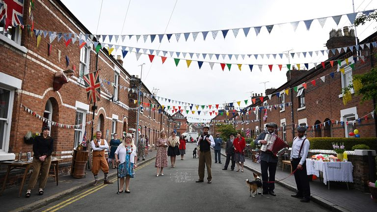 Residents of Cambrian Road dressed up in period costume maintain social distancing guidelines as they pose on their street to mark the 75th anniversary of VE Day in Chester, northwest England on May 8, 2020. (Photo by PAUL ELLIS / AFP) (Photo by PAUL ELLIS/AFP via Getty Images)