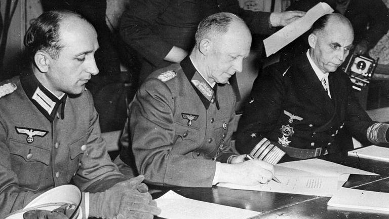 German Chief of the Operations Staff Alfred Jodl (centre) signs the unconditional surrender document