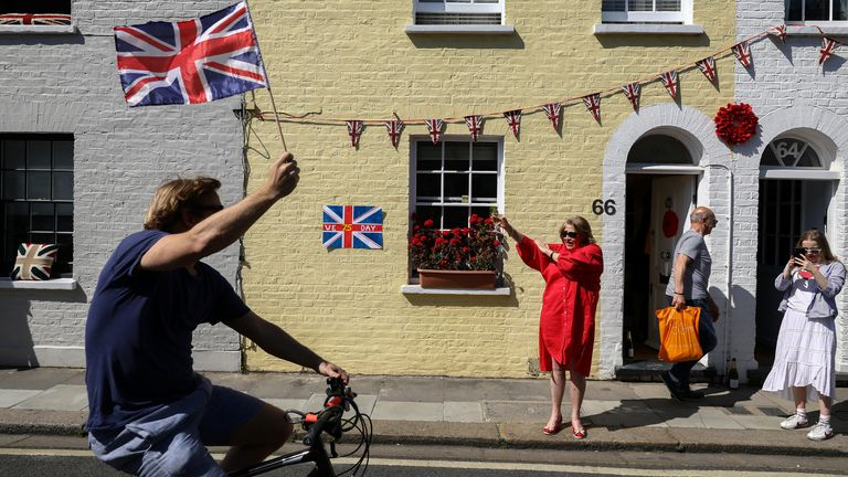 A man waves a Union flag on his bike on a street in Parsons Green, London