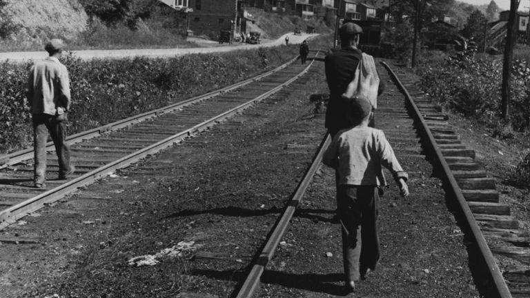People walking along train tracks to collect relief food in West Virginia in 1935
